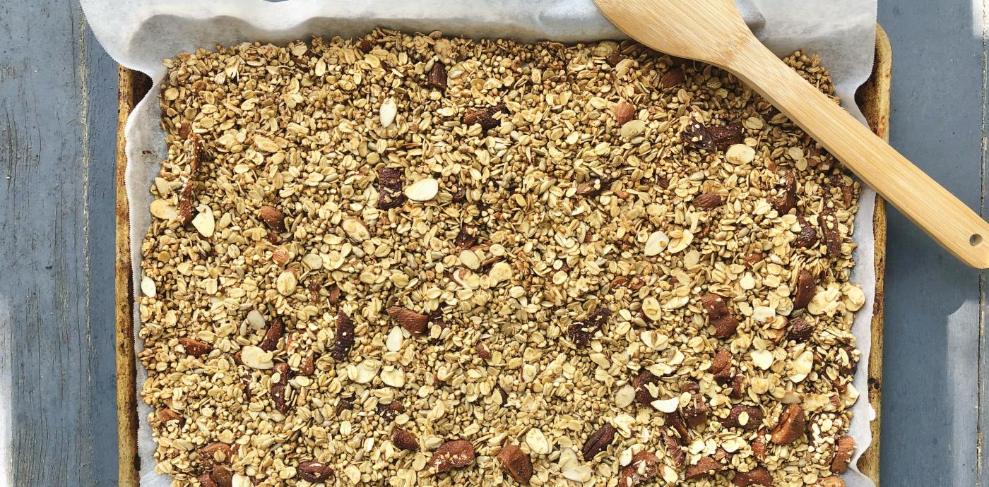 granola displayed on a parchment-lined baking sheet
