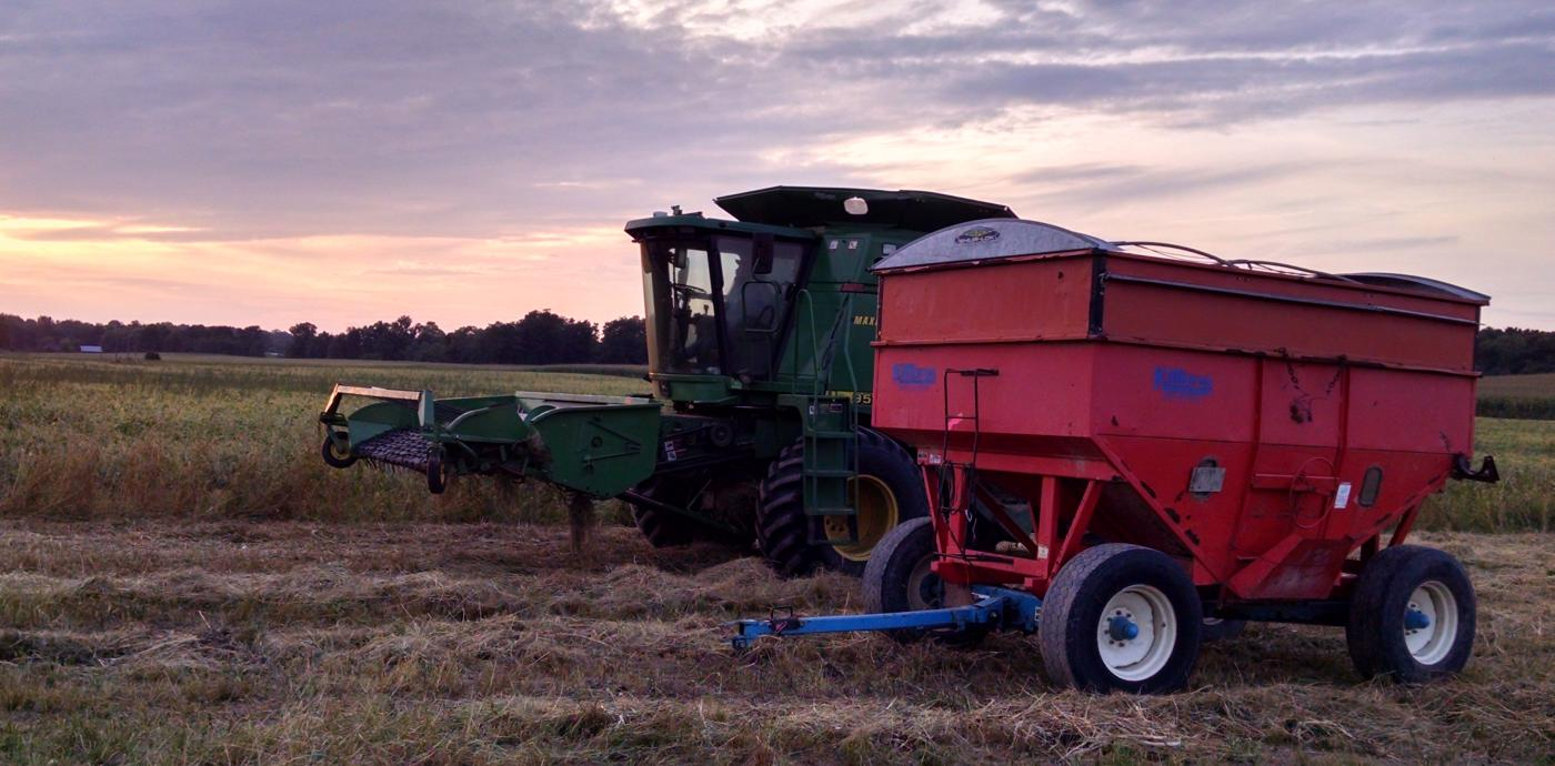 Farm equipment in field at sunset