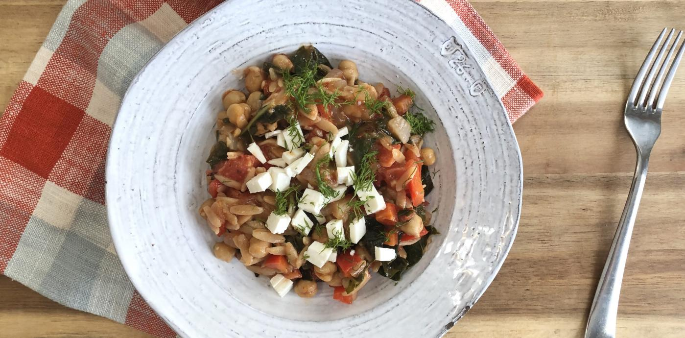 a bowl of orzo pasta and veggies in a white bowl
