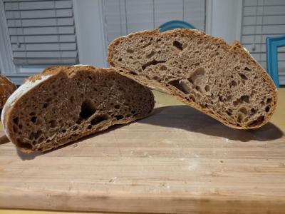 50% whole wheat loaf of bread cut in half on cutting board