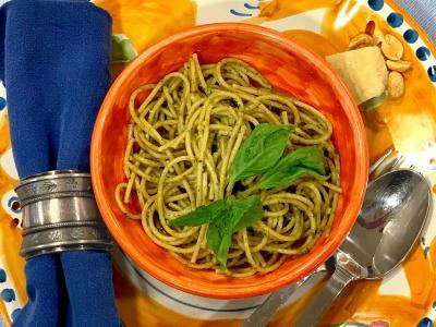 spaghetti with pesto sauce in an orange bowl