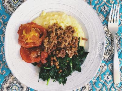 bowl on a placemat with polenta, roasted tomatoes, greens, and chorizo