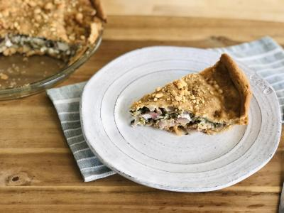 a slice of whole wheat savory pie filled with greens and cheese on a white plate