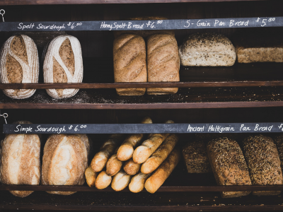 assorted artisan breads displayed on a bakery shelf
