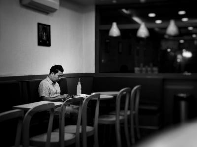 Man sitting in empty restaurant alone at table
