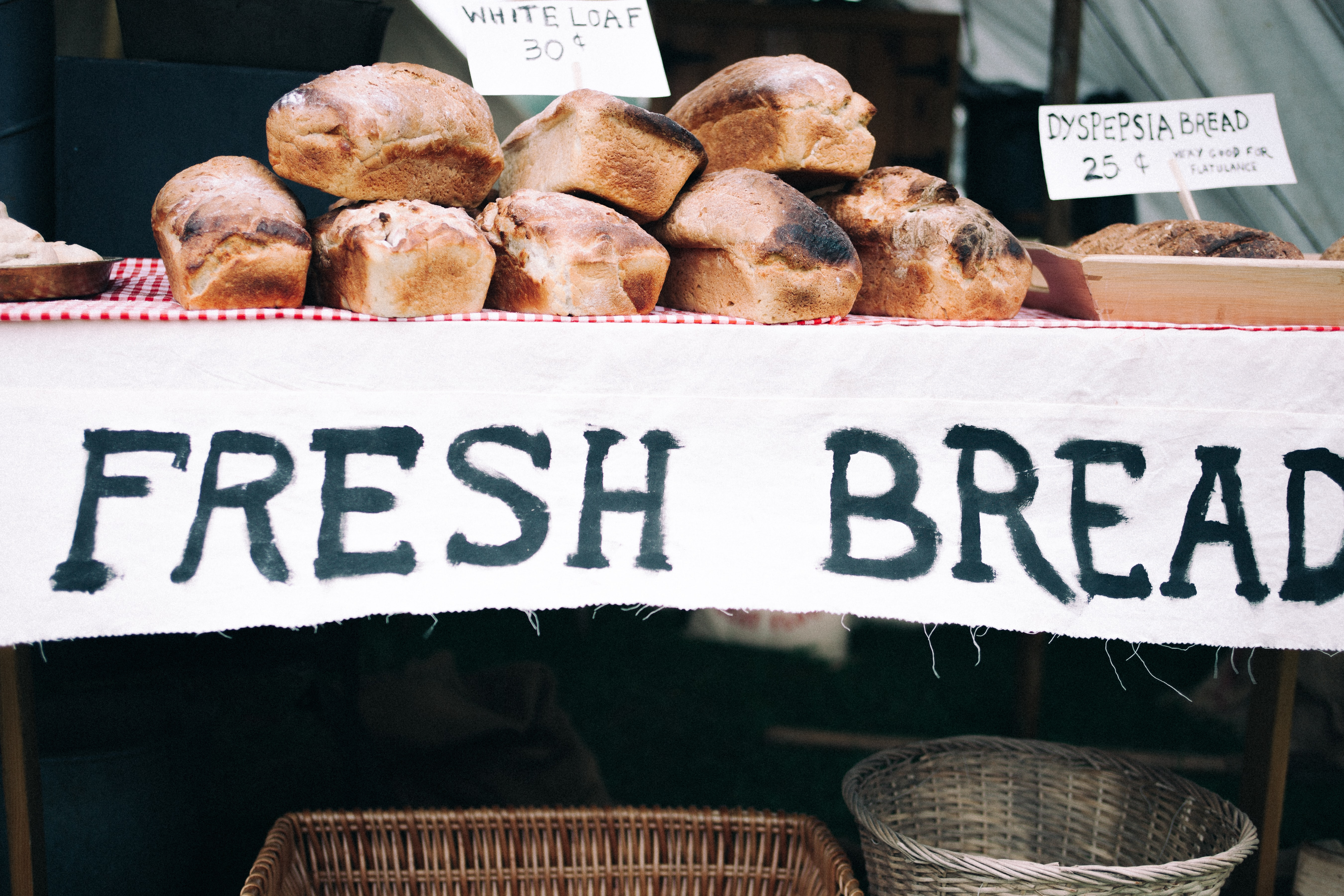 Table piled with loaves of bread with a sign reading Fresh Bread