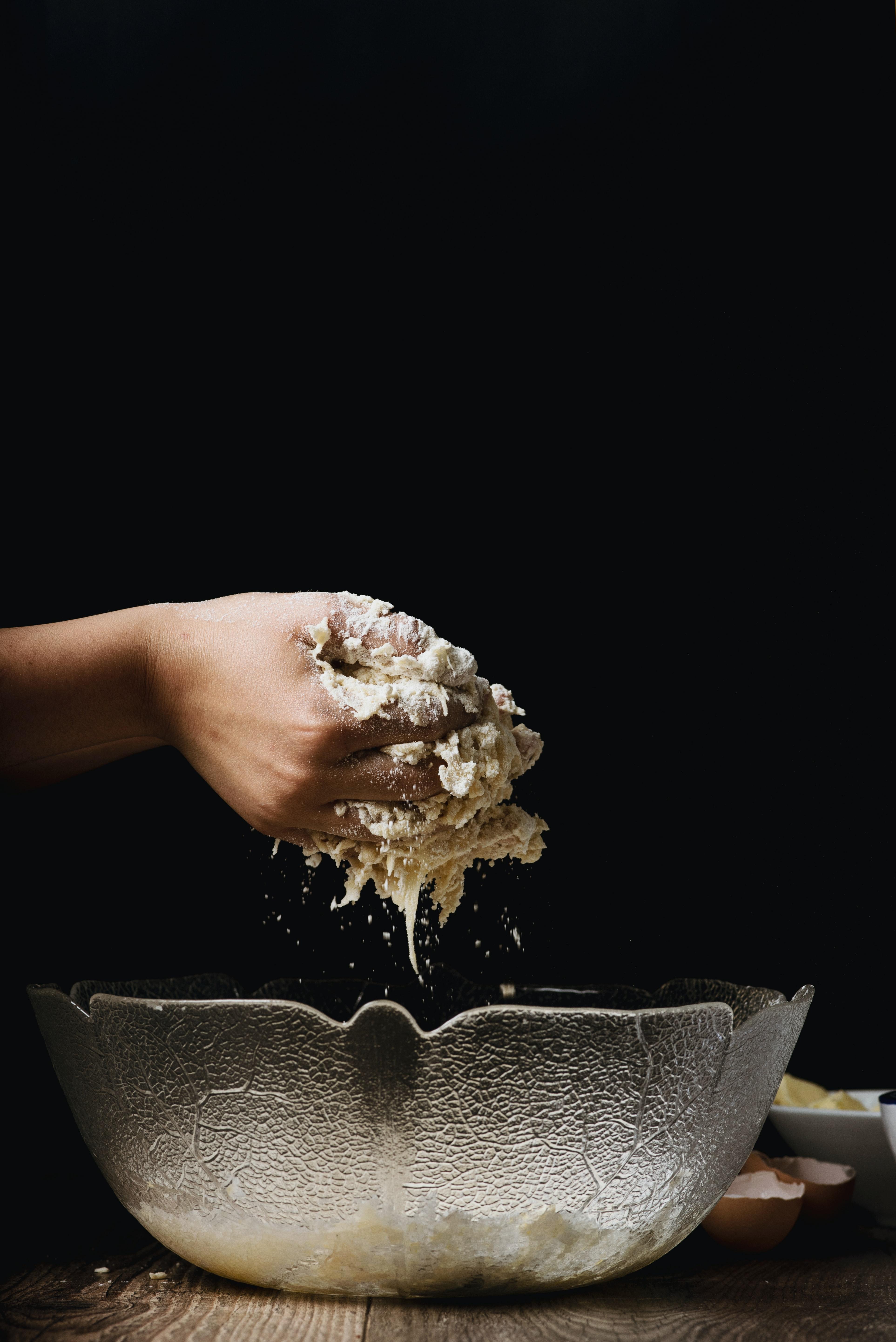 Hands mixing dough above glass bowl