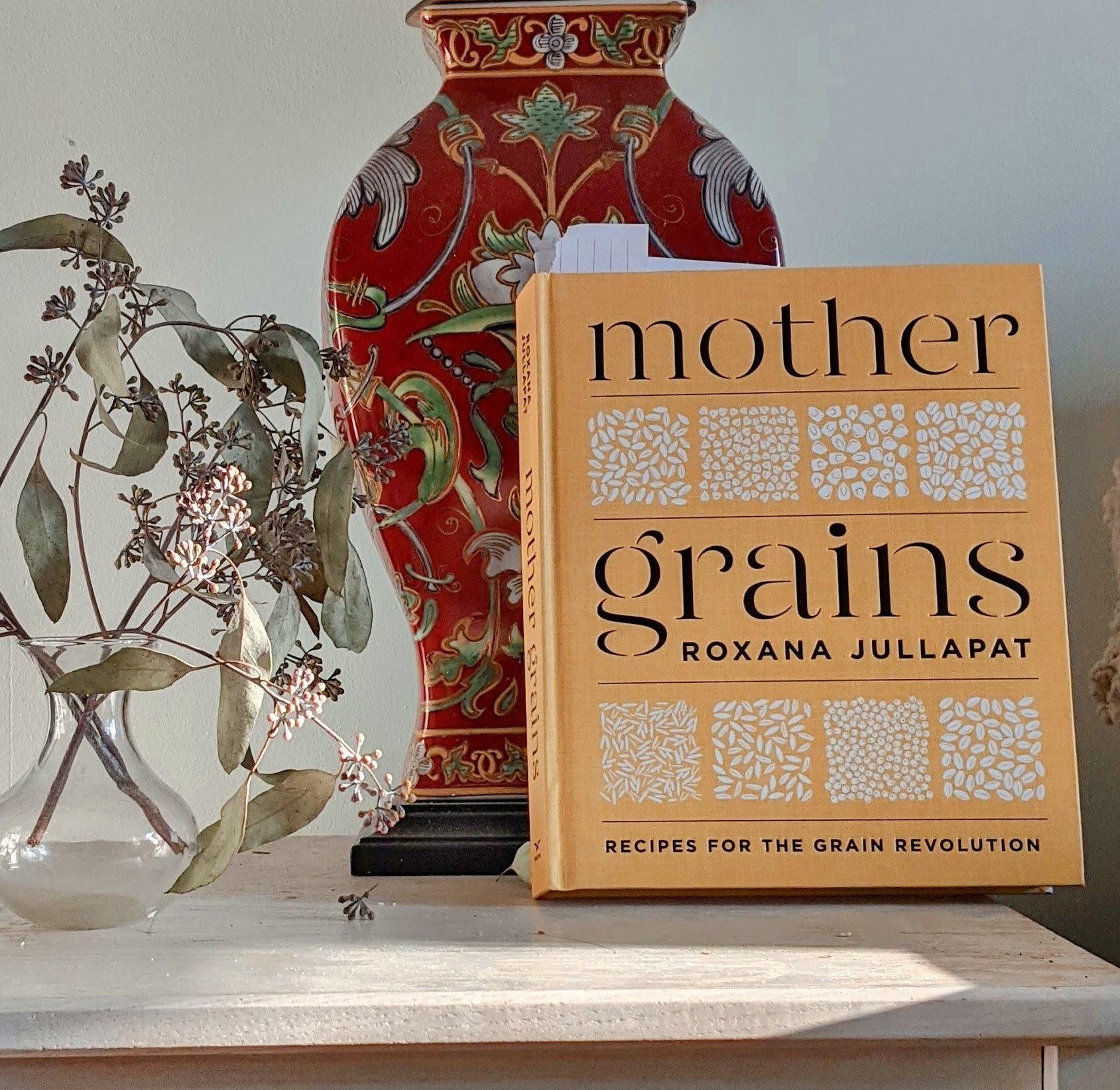 Cover of the cookbook Mother Grains, leaning on red vase with dried flowers