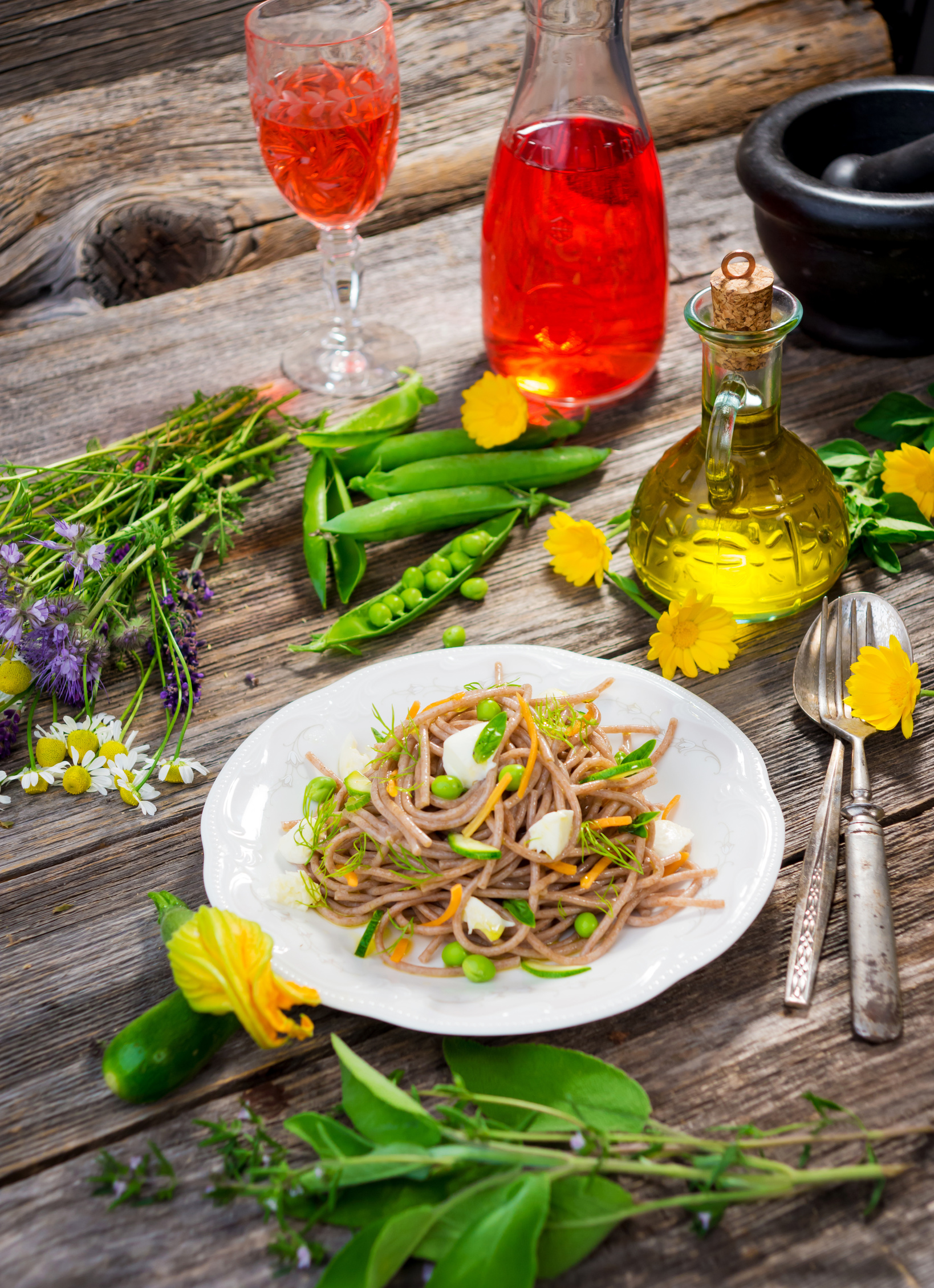 Whole Grain pasta with peas on wooden table surrounded by fresh flowers and veggies