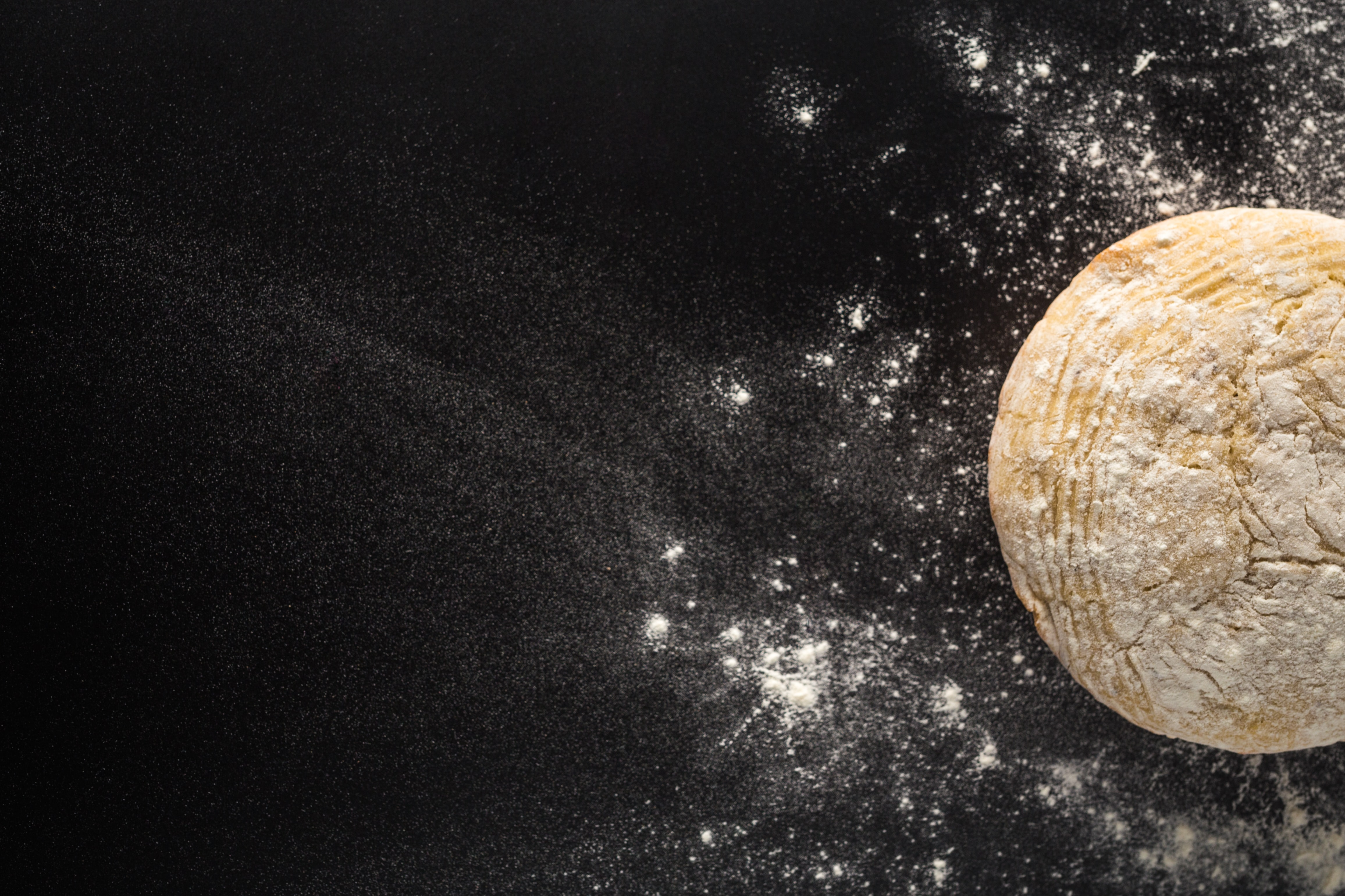 Uncooked bread loaf on black background surrounded by a sprinkle of flour