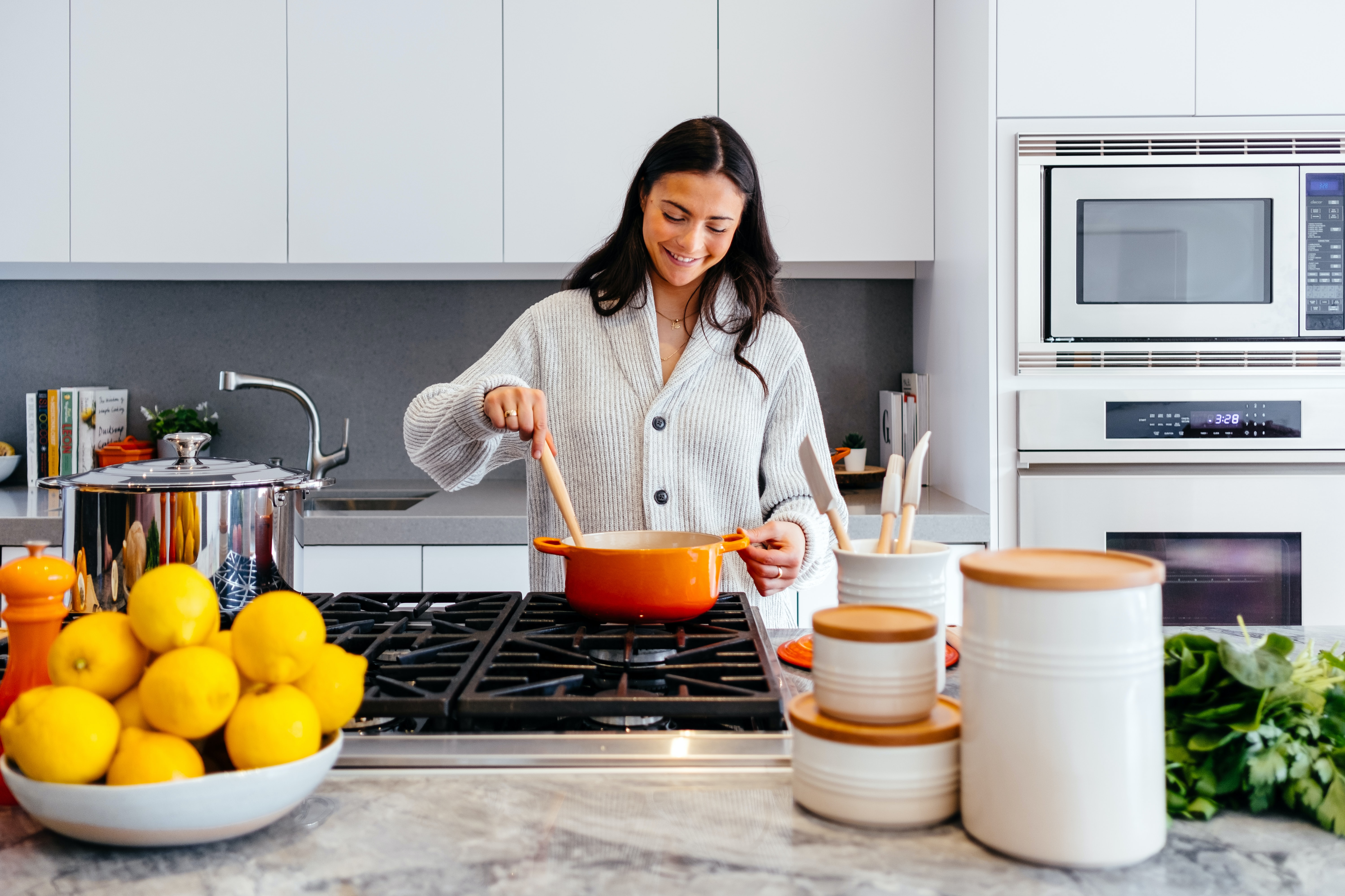 Woman in kitchen stirring a orange pot with wooden spoon