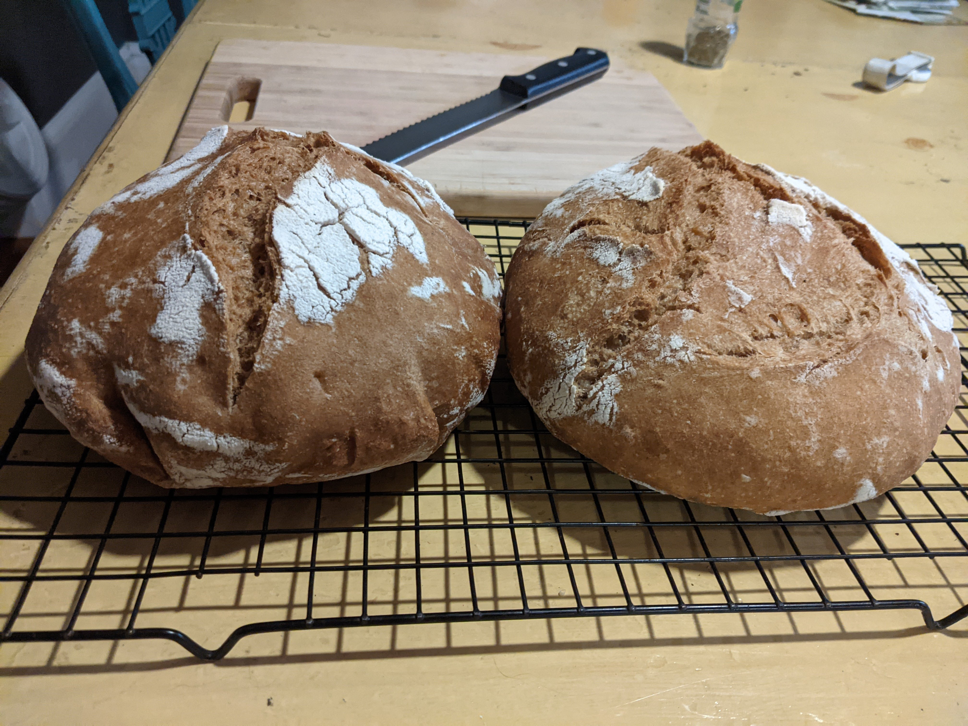 two loaves of bread side by side with cutting board and bread knife in background