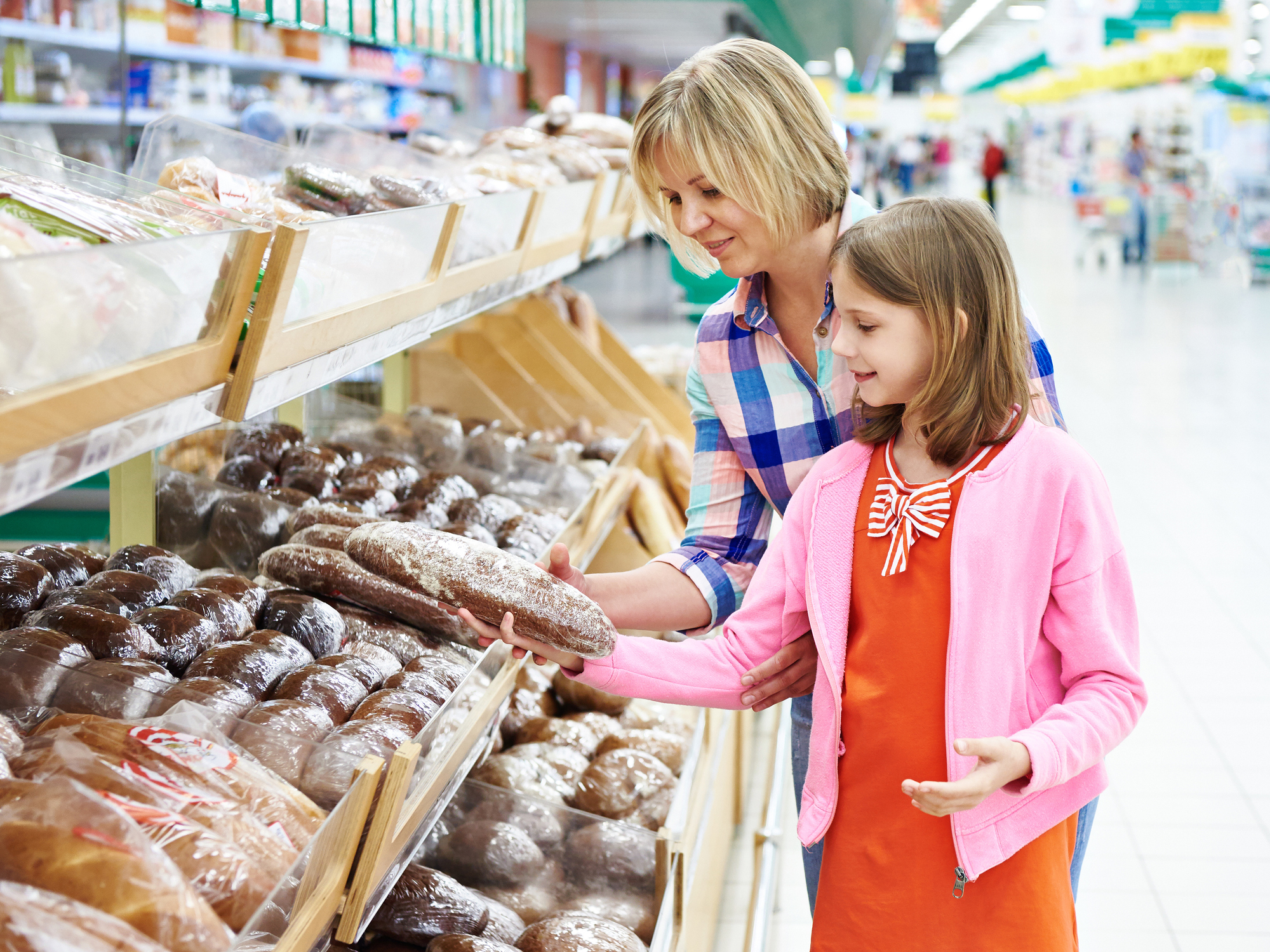 Child and parent choosing whole grain bread at grocery store