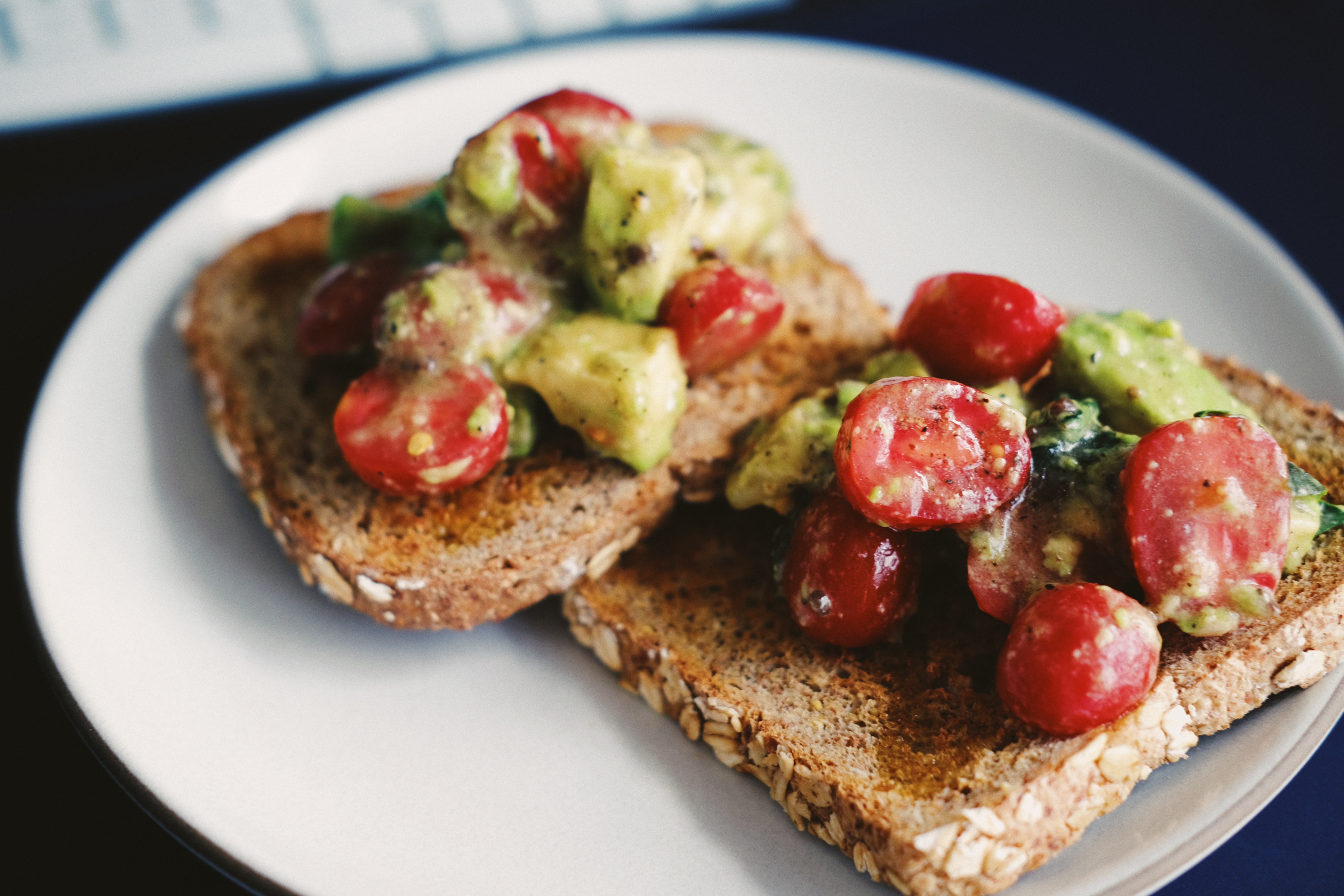 Two pieces of whole grain toast with tomatoes and avocados