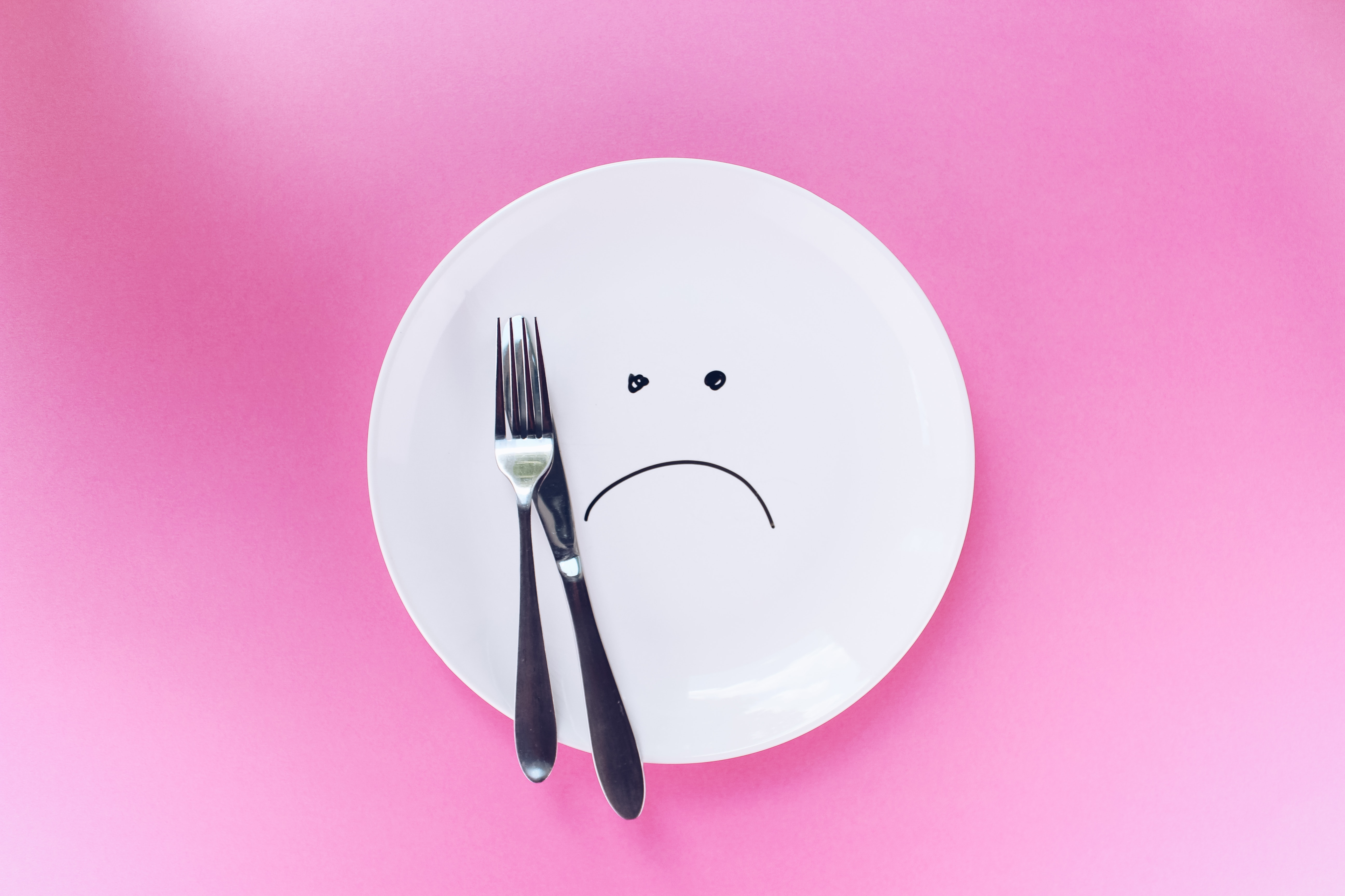 plate with frown on pink background