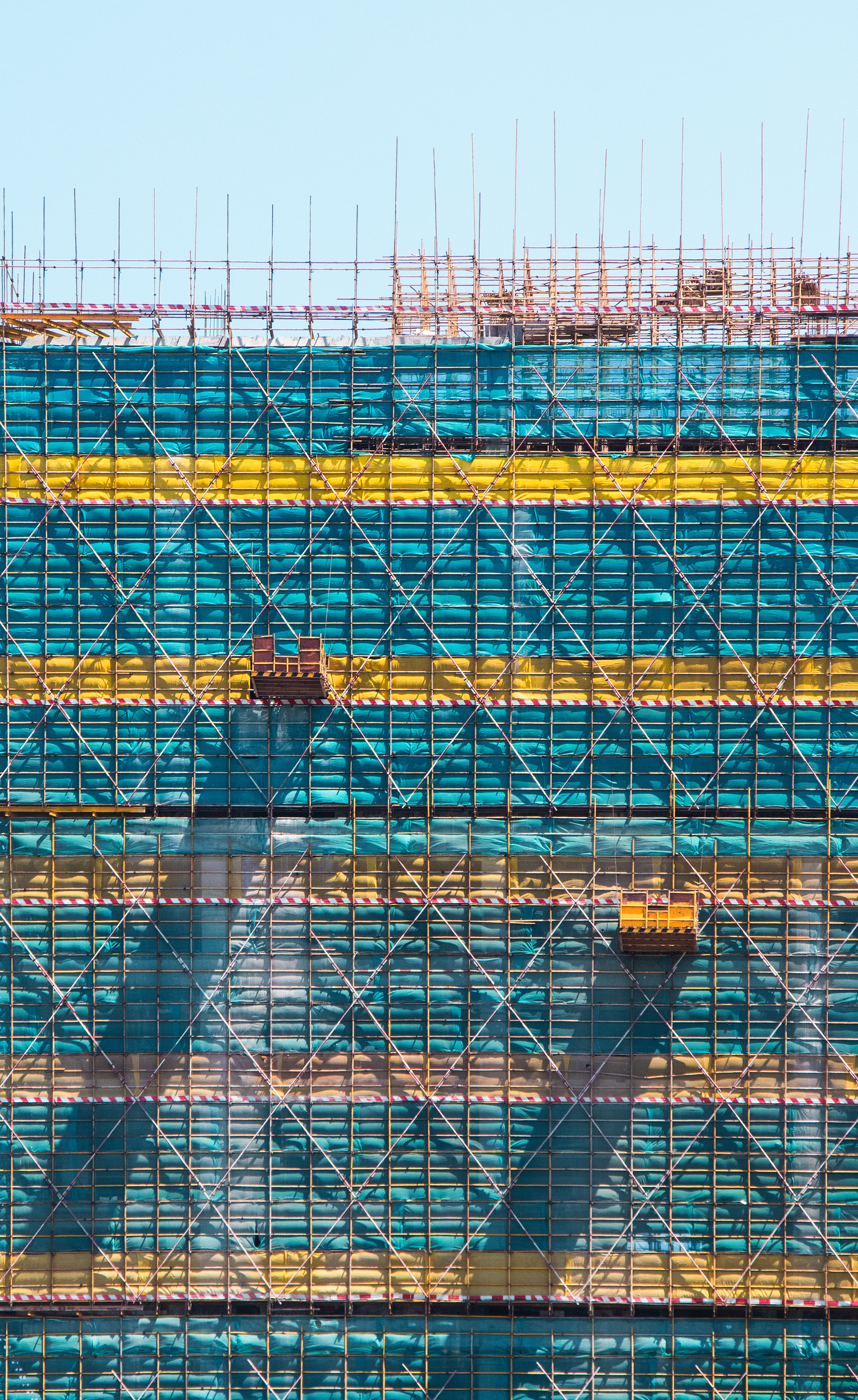 Red scaffolding on blue and yellow shipping containers
