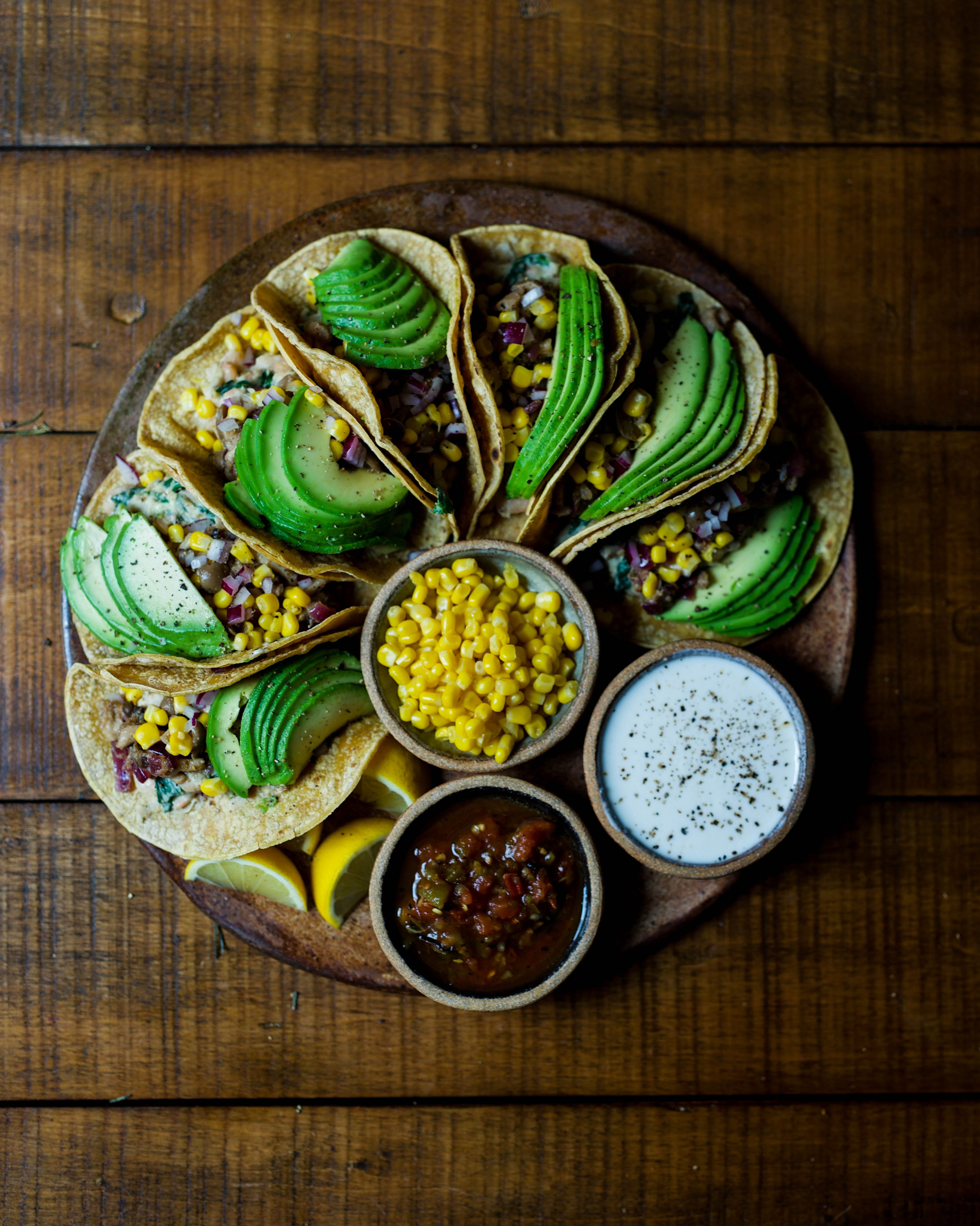 Avocado tacos arranged on a brown plate